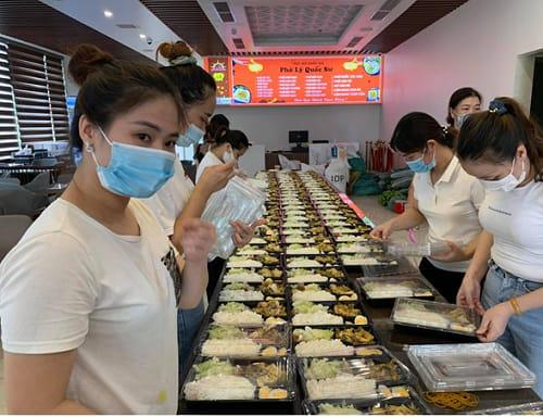 Vợ của ông Phan Thanh Hùng, cũng là Tổng giám đốc công ty (bên trái) đang cùng nhân viên sắp xếp đóng gói suất ăn