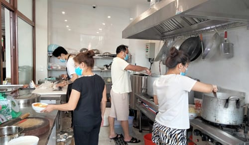 Vợ chồng ông Phan Thanh Hùng và vợ (bên phải) trực tiếp nấu ăn phục vụ người dân khu cách ly
