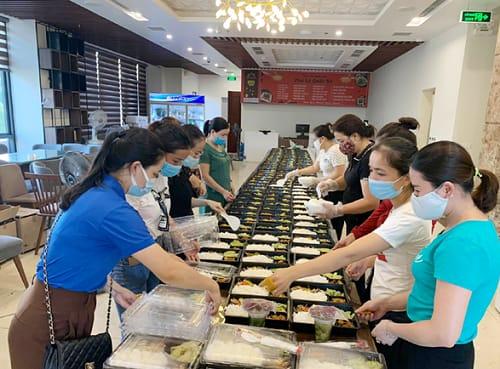 Các tình nguyện viên và nhân viên nhà hàng sắp xếp, đóng gói các suất ăn